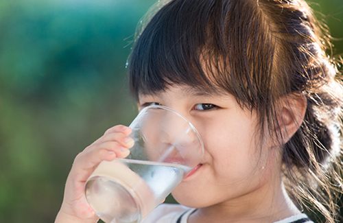 Little girl drinking water from a glass