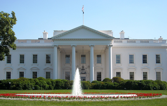 The White House on a sunny day with water fountain and colorful flowers