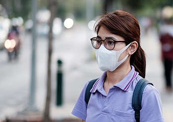 photograph of a young woman wearing a face mask and glasses. NEHA is actively monitoring and tracking the novel coronavirus outbreak.