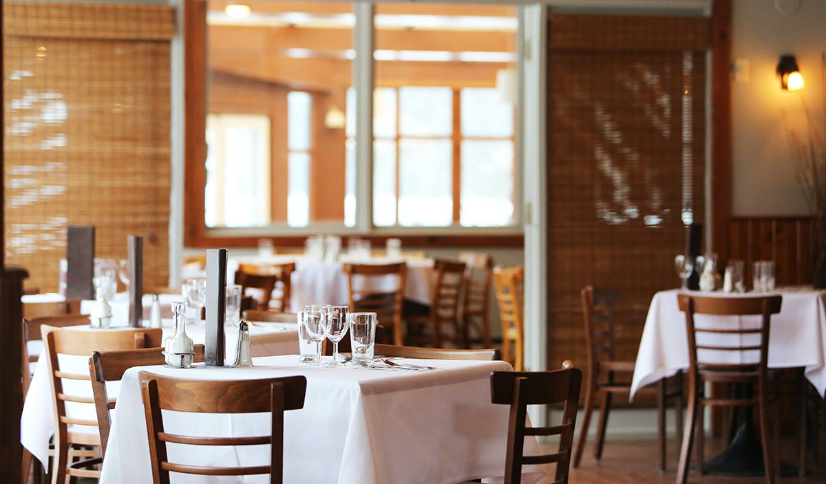 empty dining room with white table cloths and bright lighting. Join the NEHA Virtual Panel: Resuming Operations Post-COVID-19