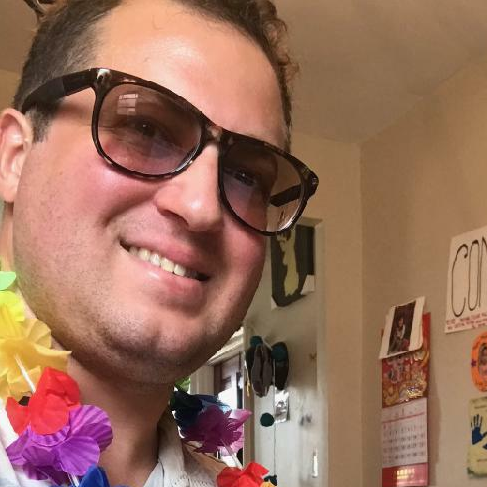 Photo of Joshua Lopez wearing sunglasses and a lei.