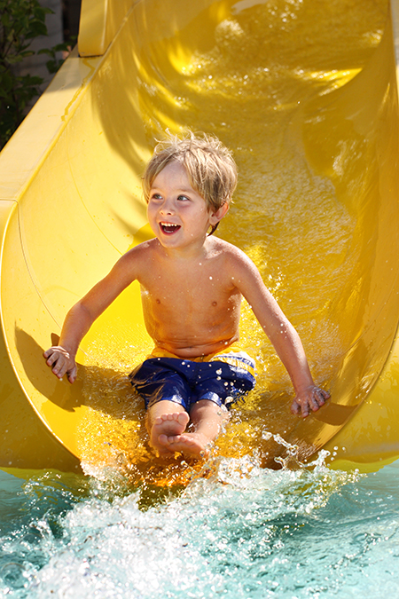 smiling little boy in blue swim-shorts sliding down a bright yellow water slide