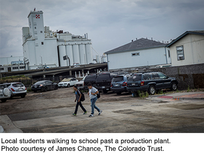 Local students walking to school past a production plant.
