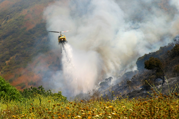Helicopter pours water over wildfire