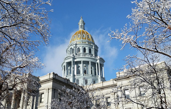 The Colorado State Capitol Building in winter with frost on the trees against a bright blue sky